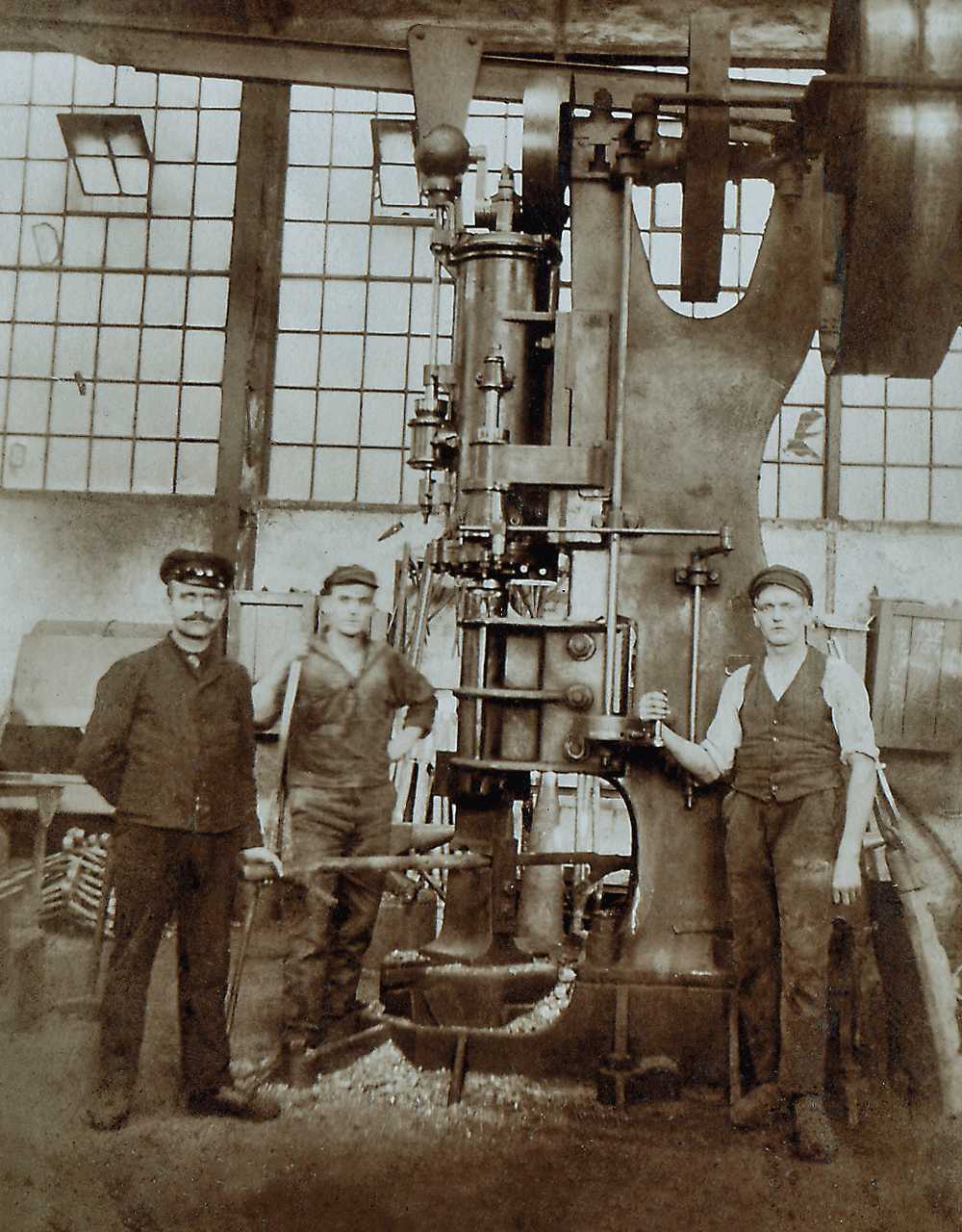 Old picture of three AERZEN employees in front of an AERZEN unit